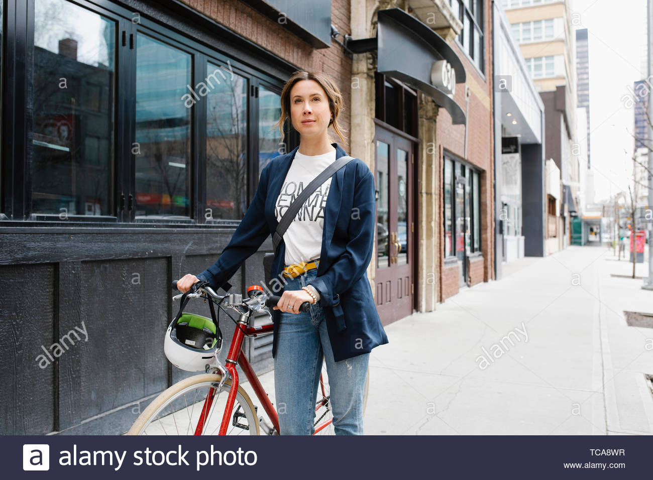 Confident woman walking with bicycle on urban sidewalk - Stock Image