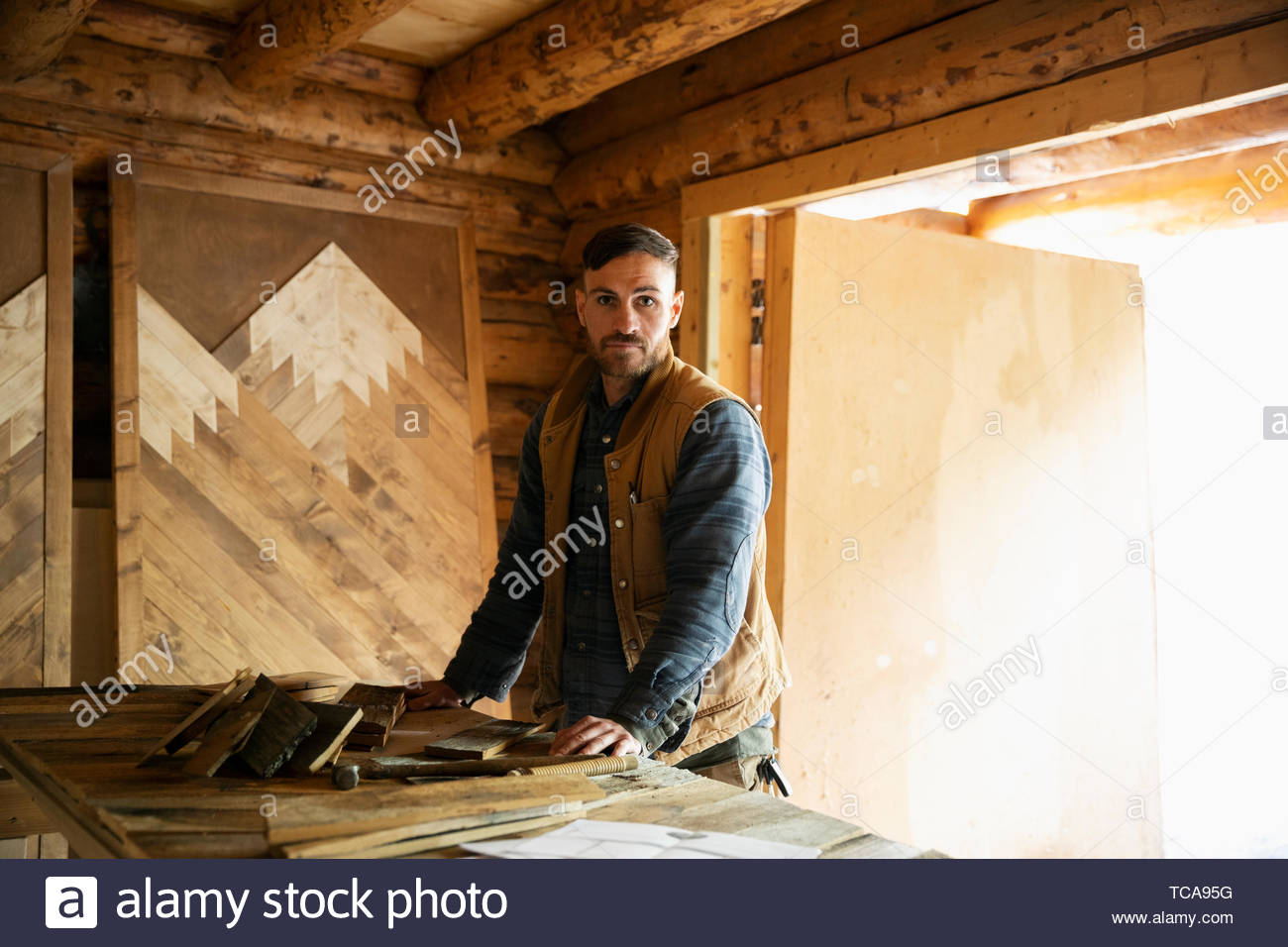 Portrait confident man woodworking in workshop - Stock Image