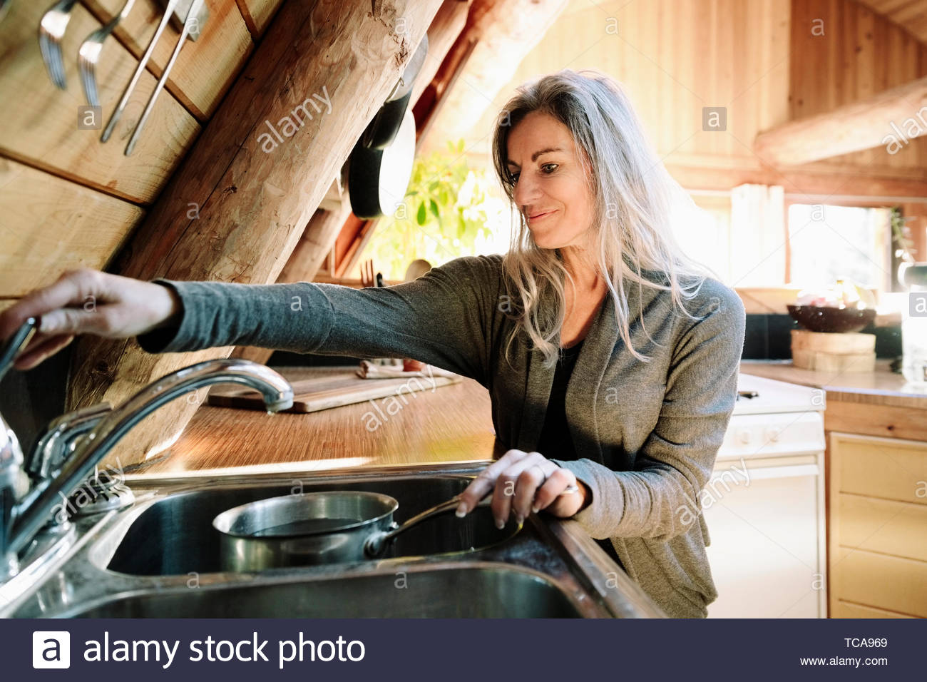 Woman filling pot with water, cooking in cabin kitchen - Stock Image