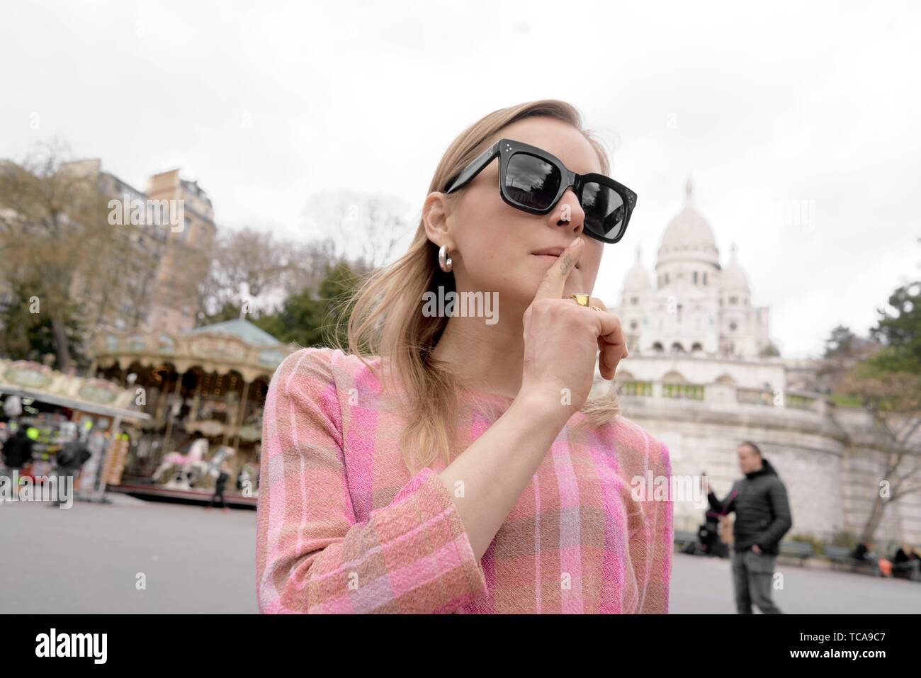stylish blogger woman in front of touristic sight Basilica Sacré-Cœur, silence fingers in front of lips, during fashion week, in city Paris, France, Stock Photo