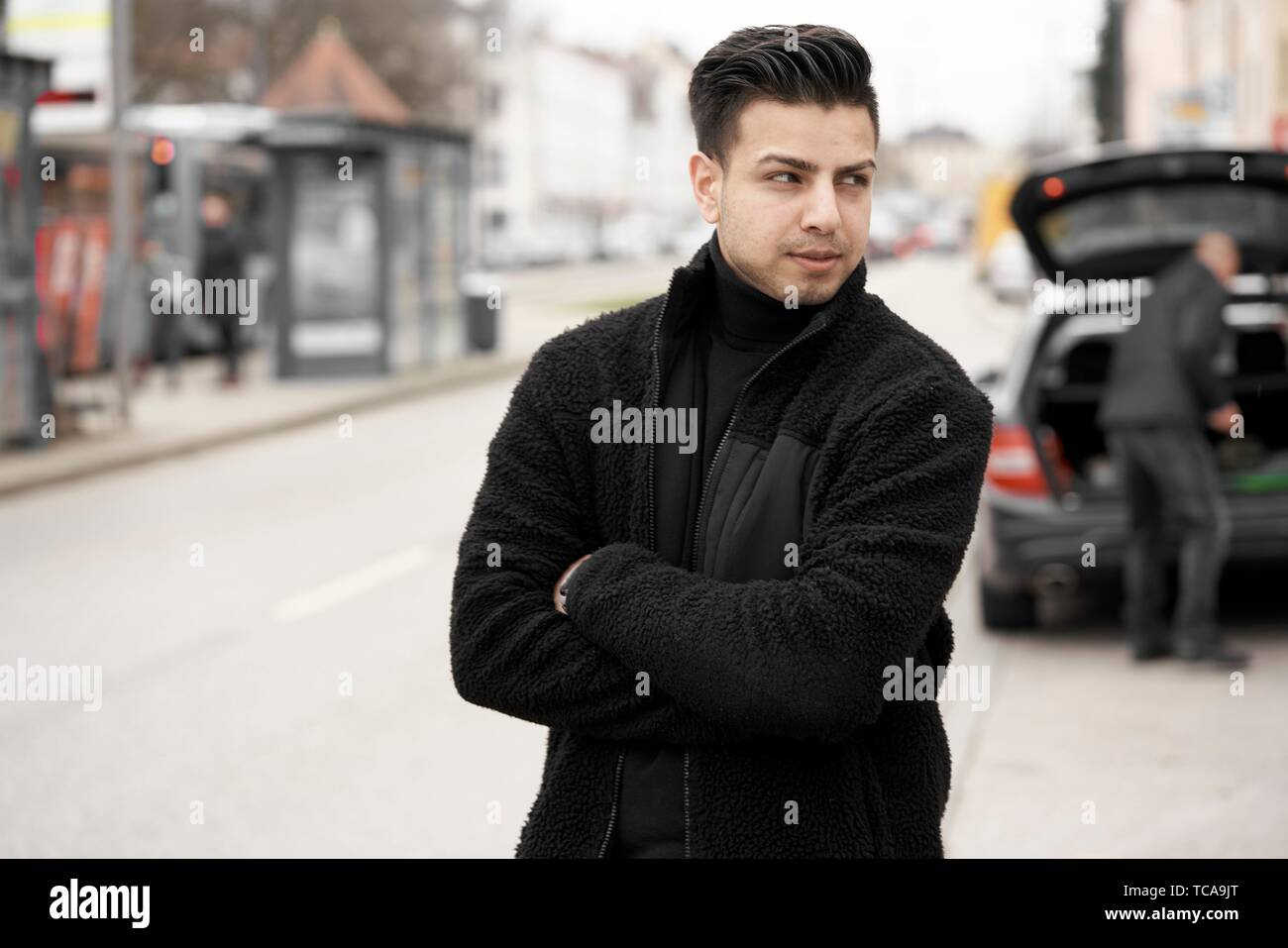 young man with crossed arms at street, looking back at man packing car for trip, turned away, in Munich, Germany. Stock Photo