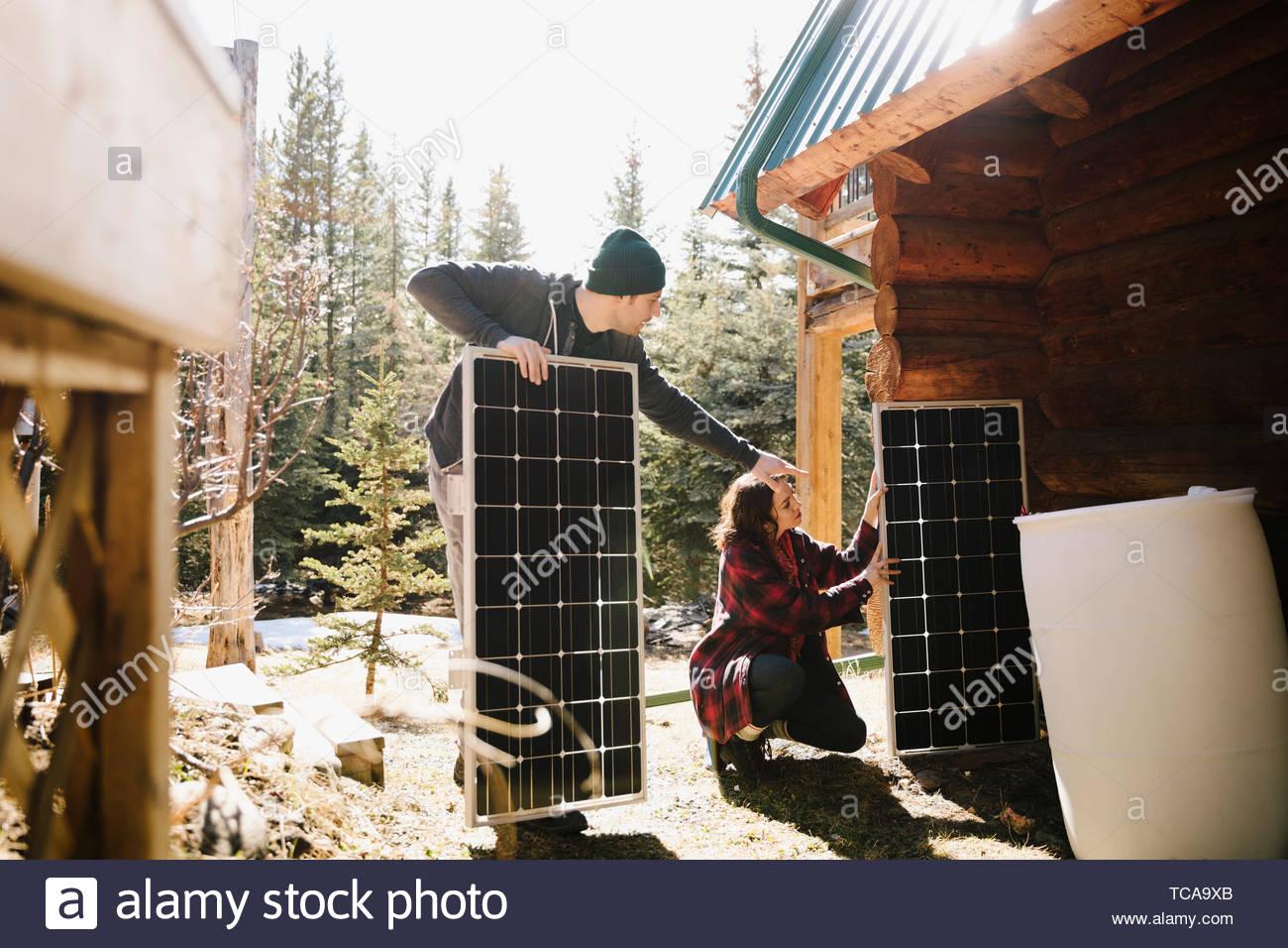 Couple installing solar panels outside cabin - Stock Image