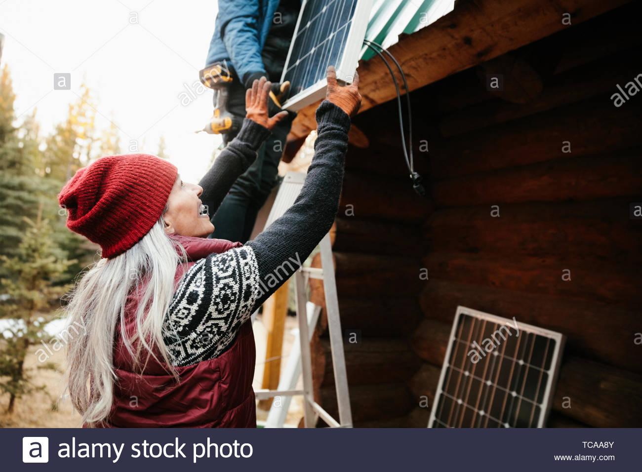 Happy woman installing solar panels on cabin - Stock Image