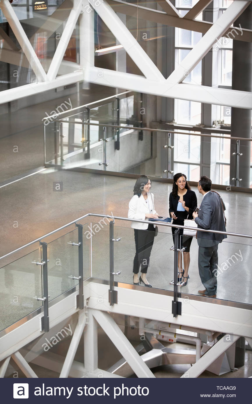 Business people talking on office atrium balcony Stock Photo