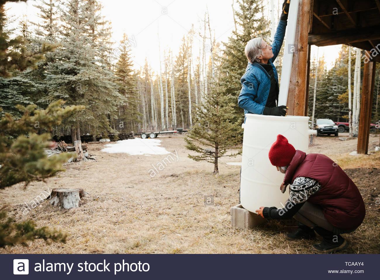 Couple installing rain barrel outside cabin Stock Photo