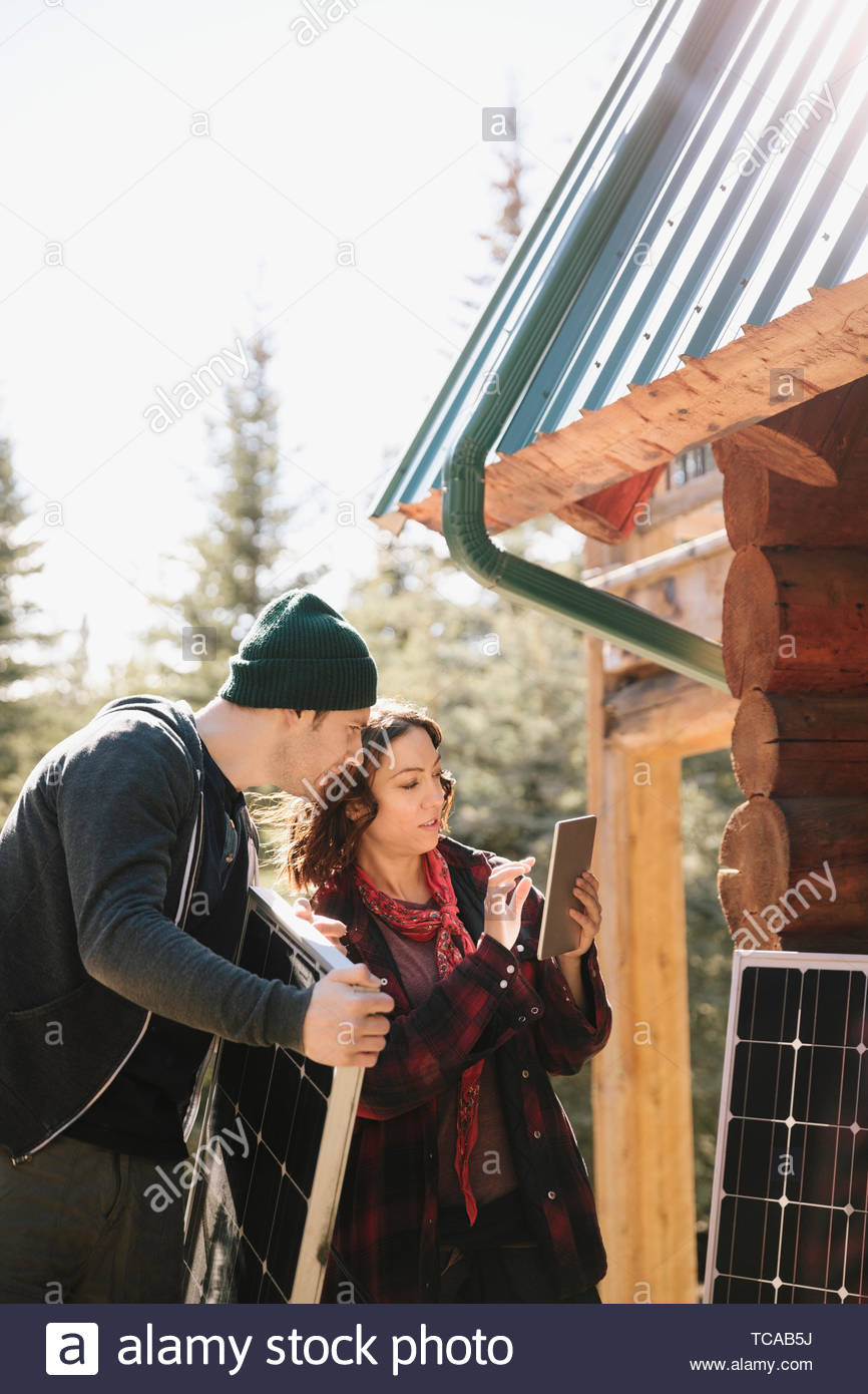 Couple with digital tablet installing solar panels outside cabin - Stock Image