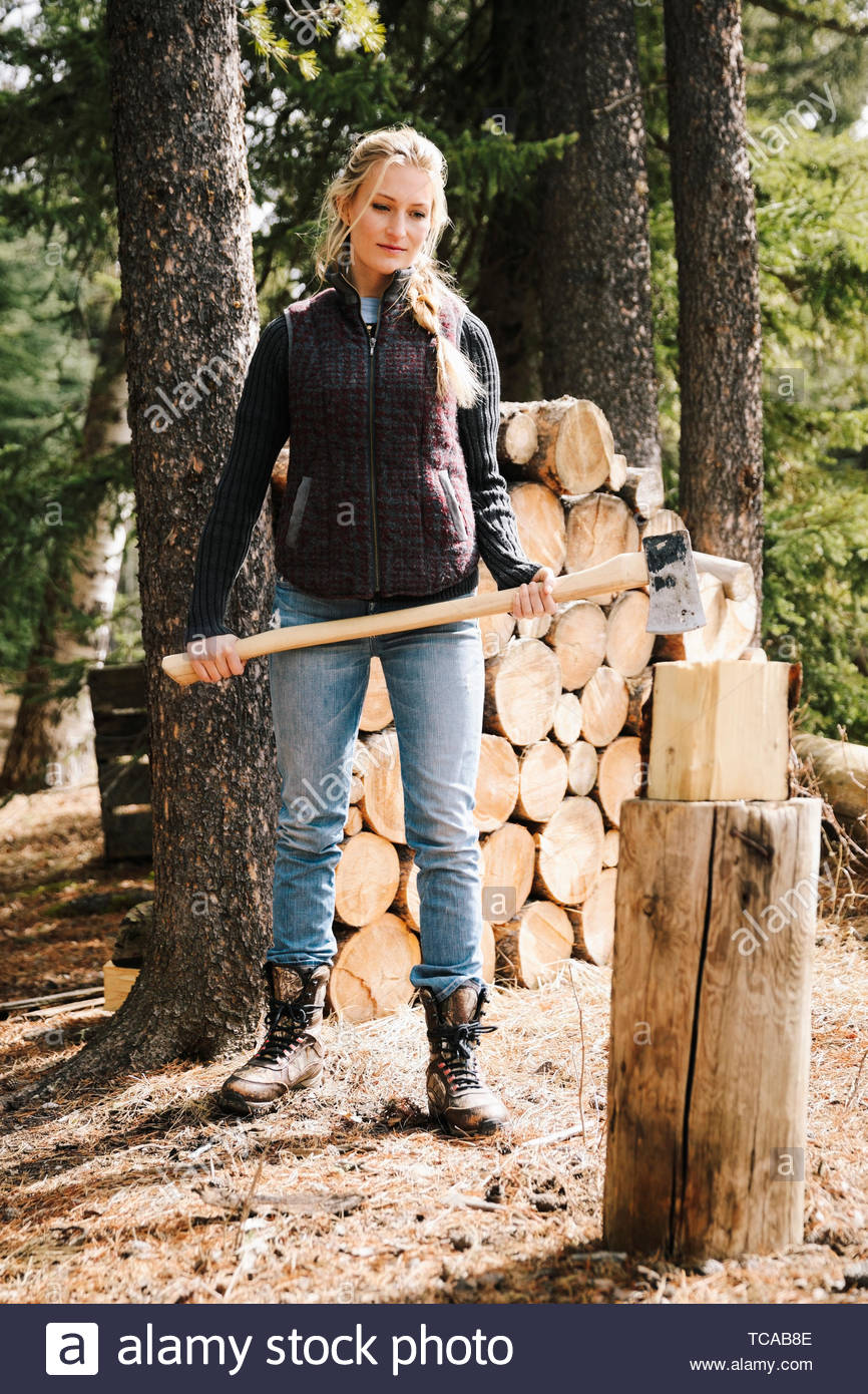 Woman with ax splitting firewood - Stock Image