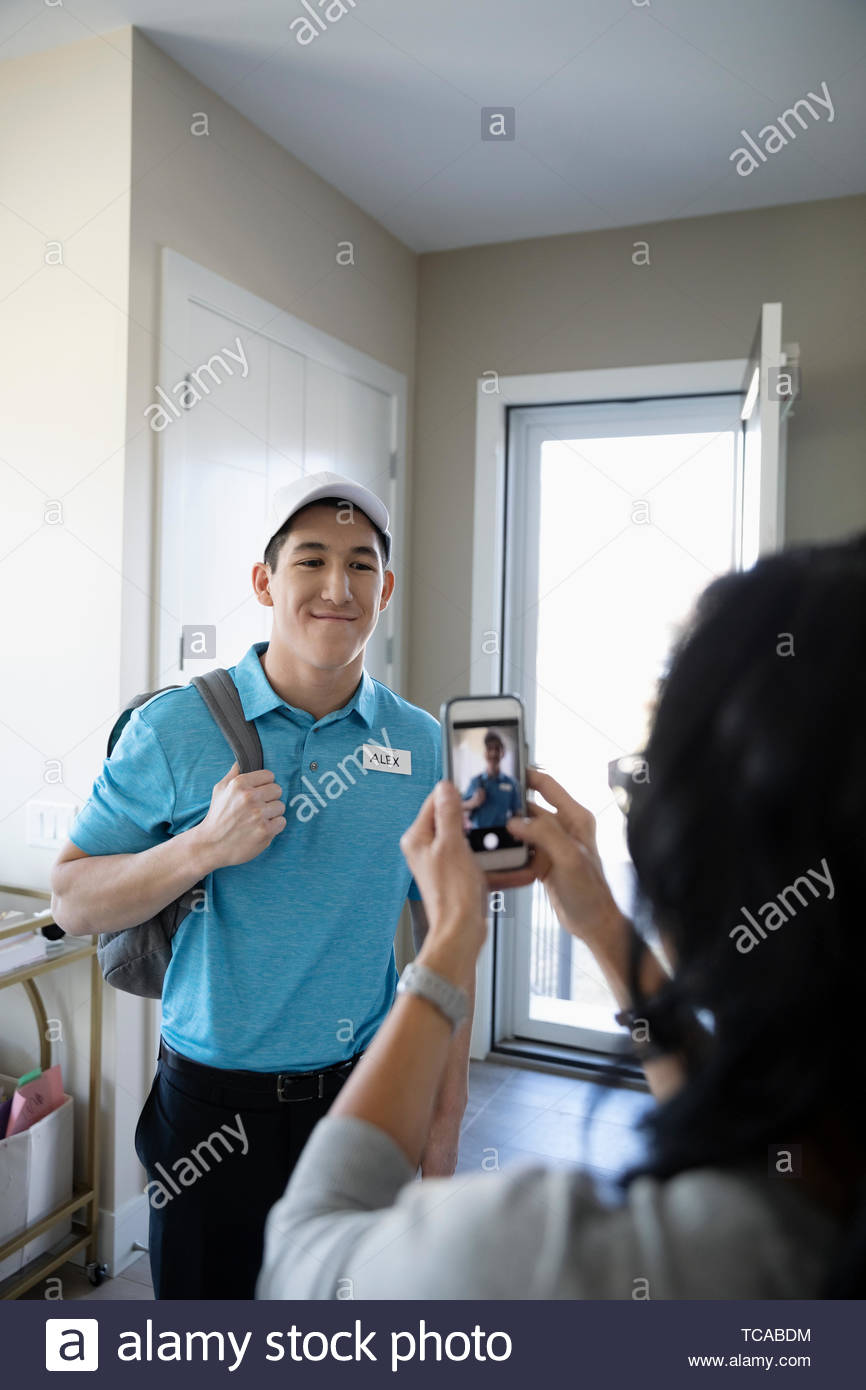 Mother with camera phone photographing teenage son in work uniform Stock Photo