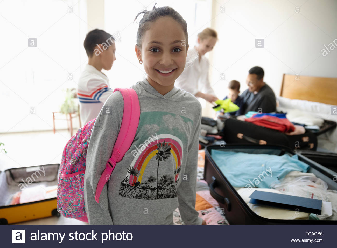 Portrait smiling, confident girl helping family pack suitcases - Stock Image