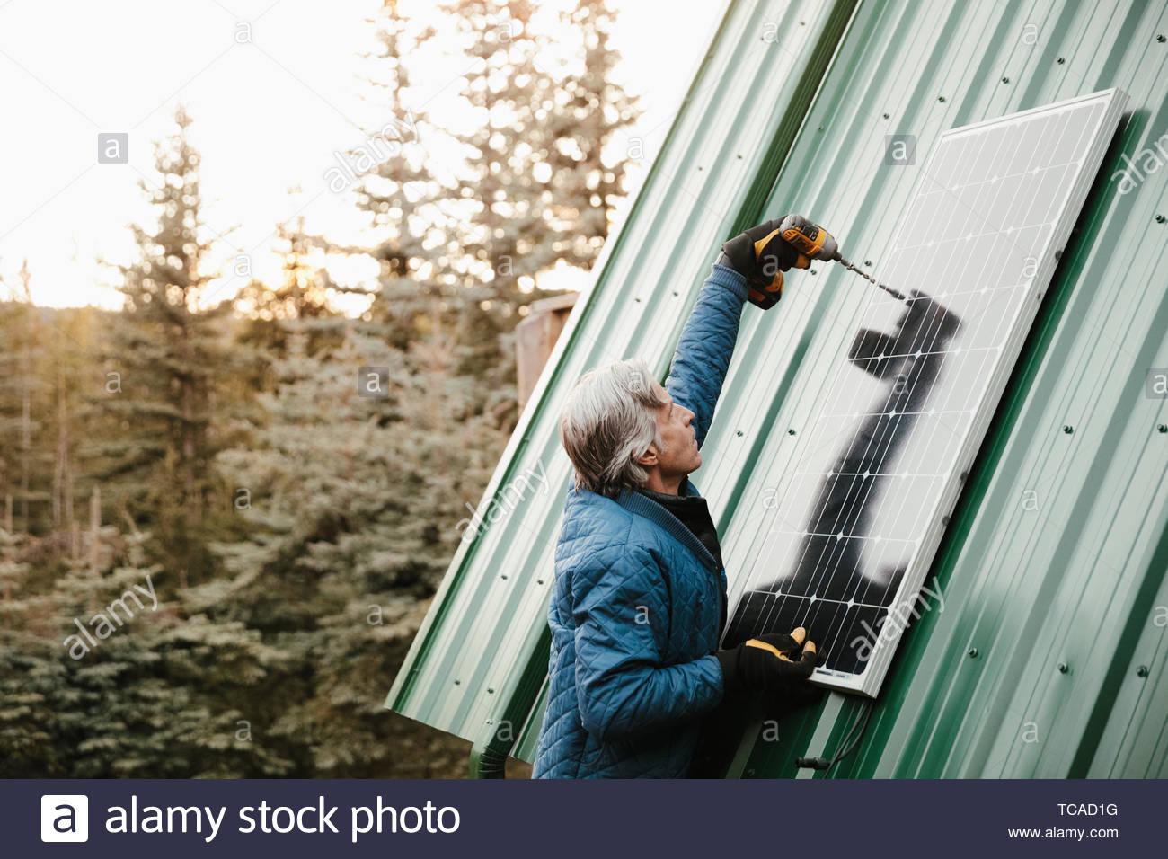 Man installing solar panel on cabin roof - Stock Image