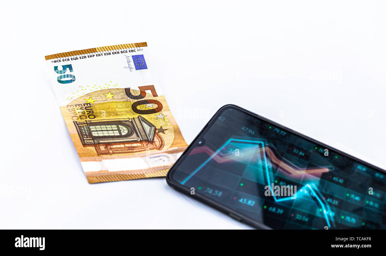 Smartphone with graphics and € 50 bill on white background, concept of investment, selective focus - Stock Image