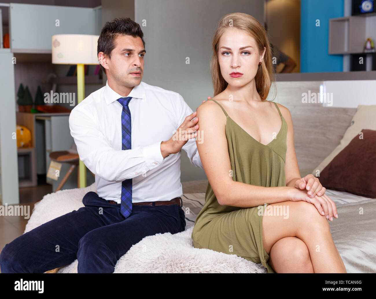 Handsome man trying to apologize to his offended girlfriend after quarrel at home - Stock Image