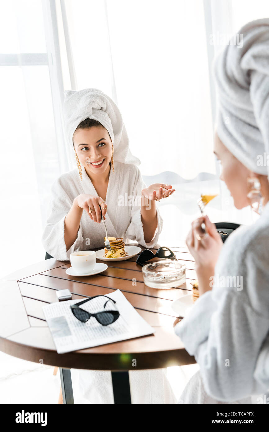 stylish smiling women in bathrobes and jewelry with towels on heads talking while having breakfast Stock Photo