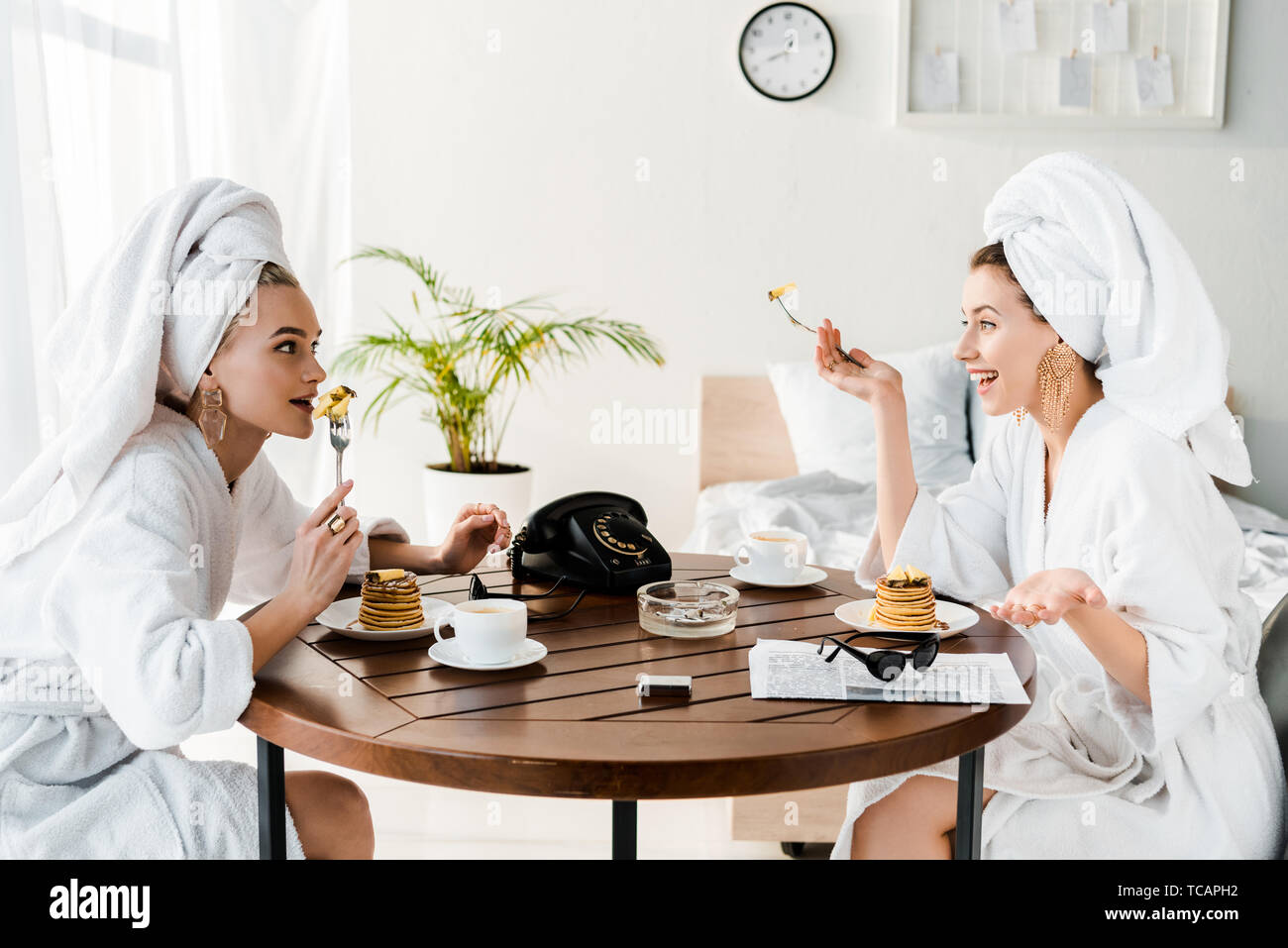 stylish happy women in bathrobes and jewelry with towels on heads talking during breakfast Stock Photo
