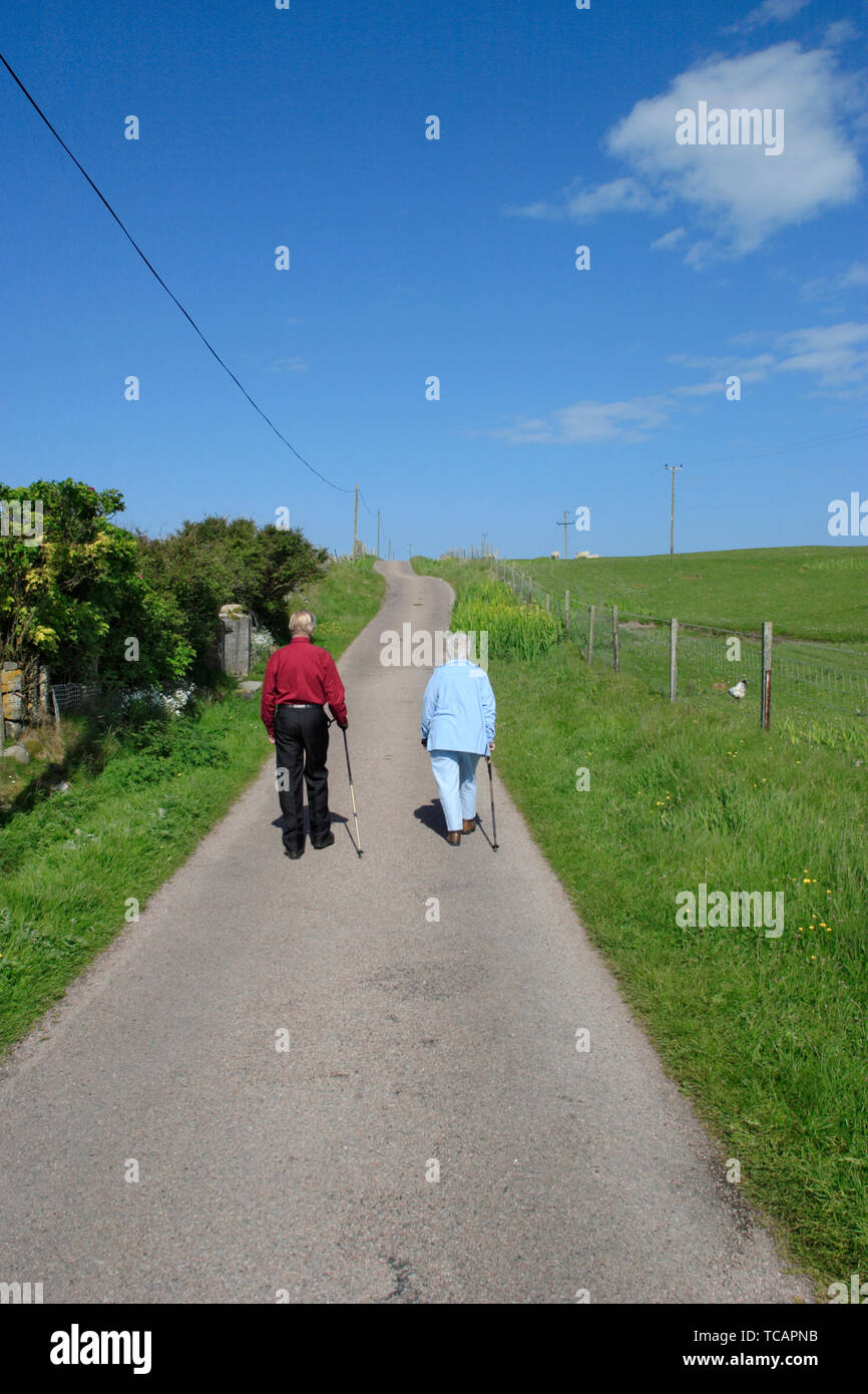 Senior citizens walking on a road in the countryside - Stock Image