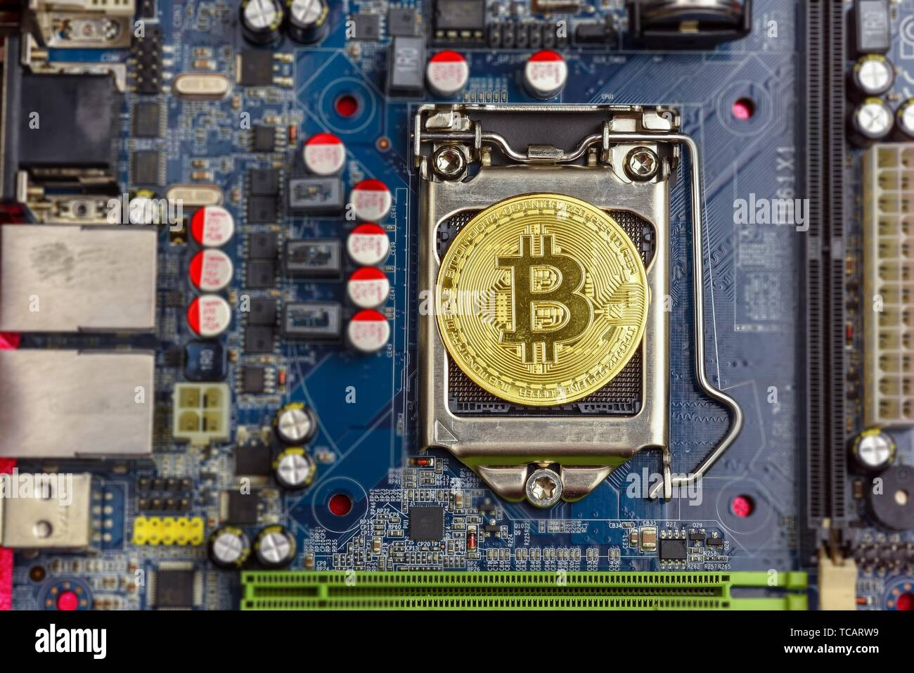 Top view of golden bit coin on computer mother board processor. Bitcoin mining farm, working computer equipment concept. Stock Photo