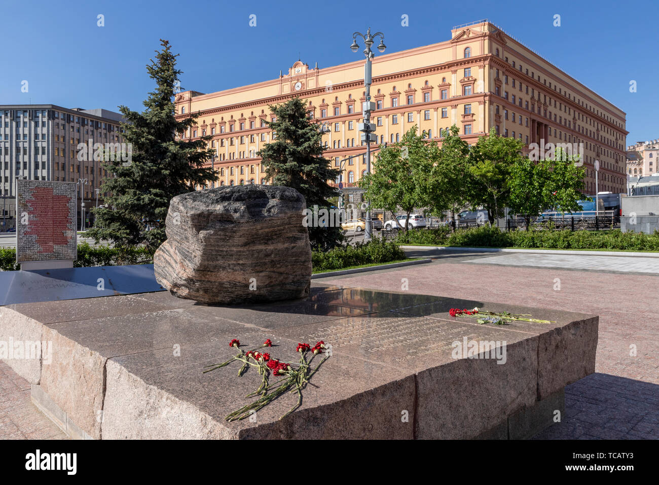 Solovetsky Stone commemorating Soviet era gulag & deportations with the notorious ex-KGB & NKVD headquarters beyond on Lubyanka Square, Moscow, Russia - Stock Image