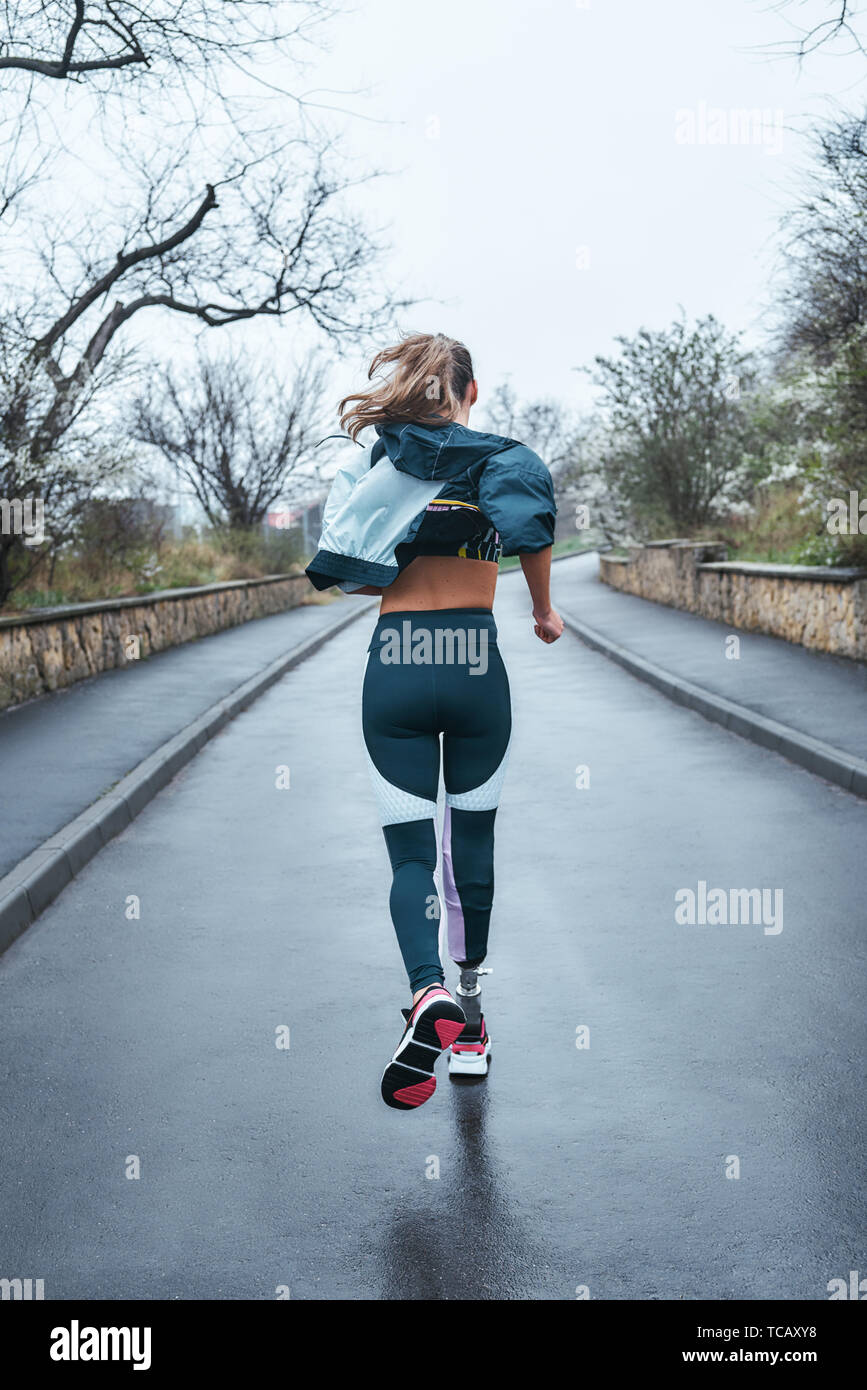 ab67bb5e81de93 You can do it Back view of strong disabled woman with bionic leg in  sportswear is