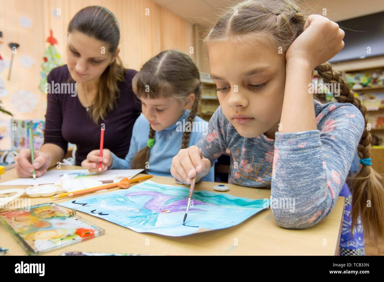 The teacher helps the students in drawing class. - Stock Image