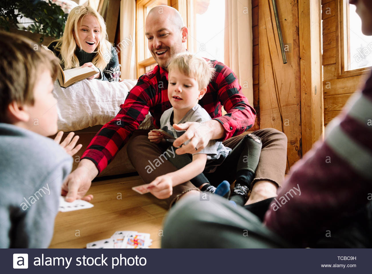 Family playing cards in cabin - Stock Image