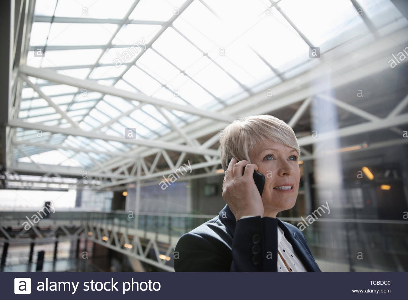 Businesswoman talking on smart phone in office atrium - Stock Image
