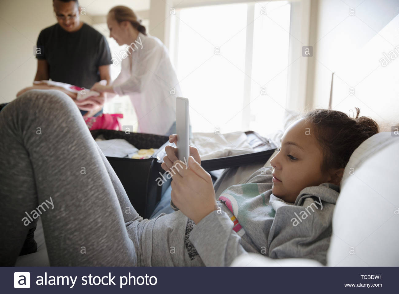 Girl using digital tablet on bed while parents pack suitcases for vacation - Stock Image