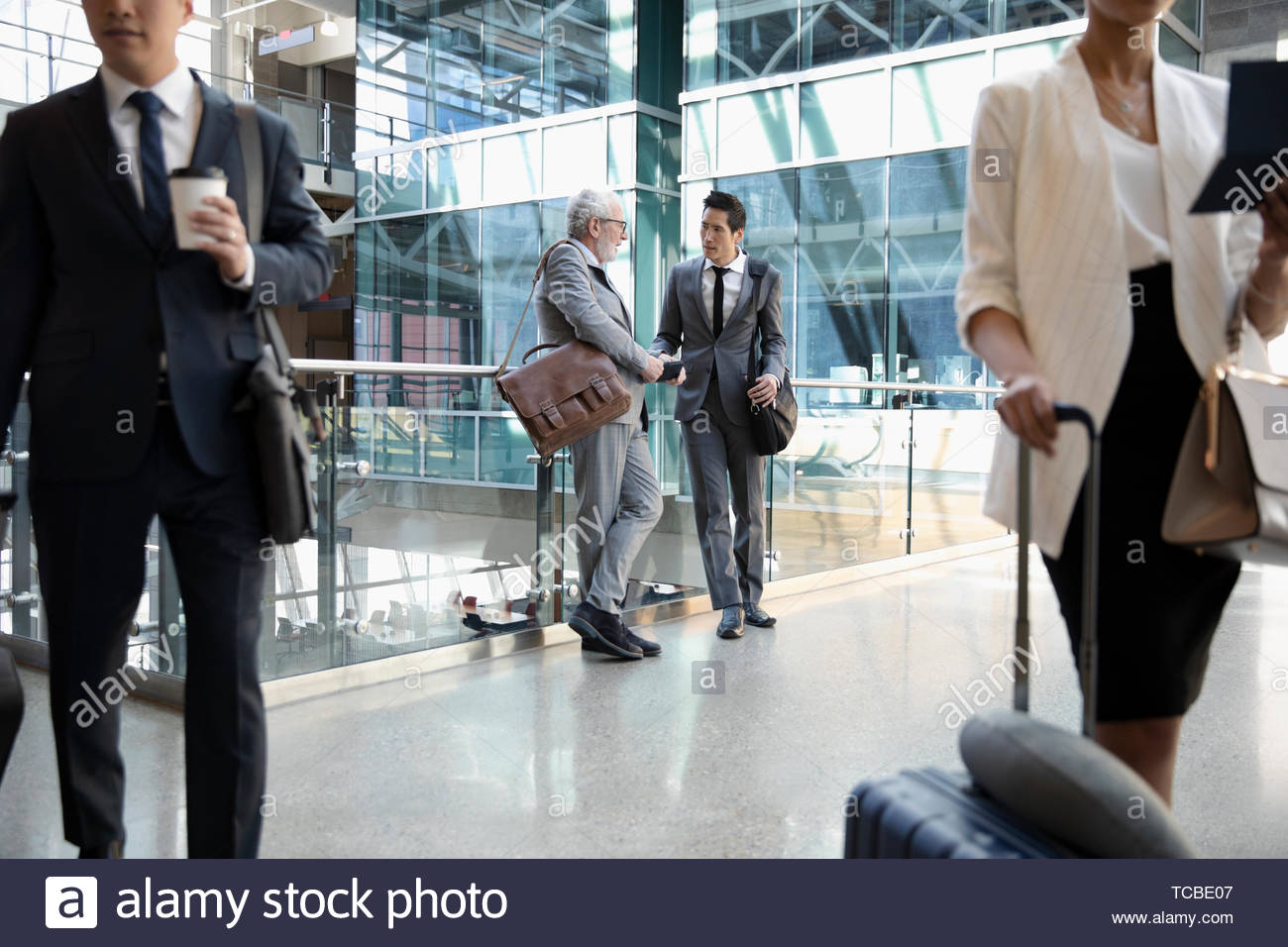 Businessmen with suitcases talking in airport - Stock Image