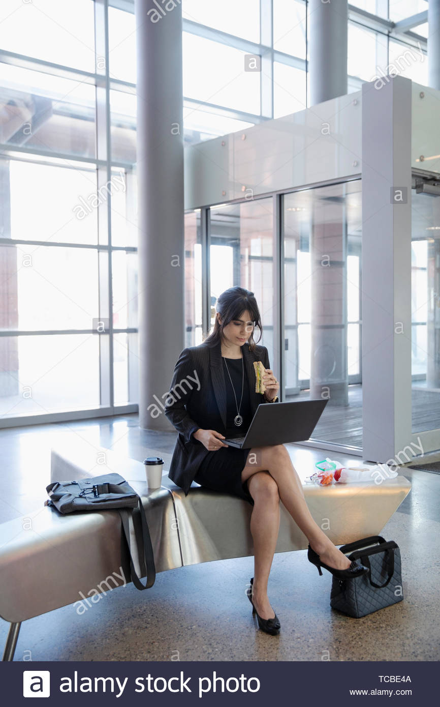 Businesswoman eating sandwich, working at laptop in office lobby - Stock Image