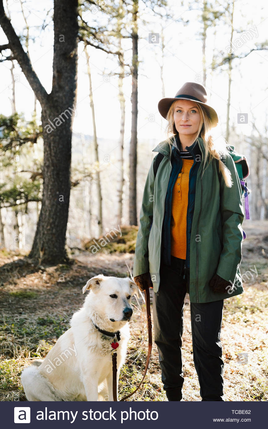Portrait confident woman with dog hiking in woods - Stock Image