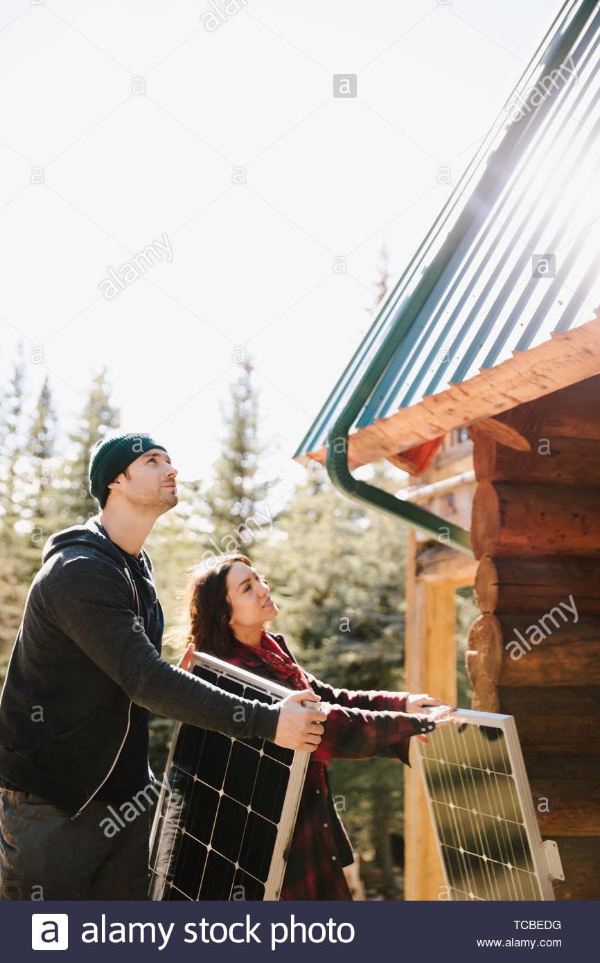 Couple installing solar panels on cabin - Stock Image