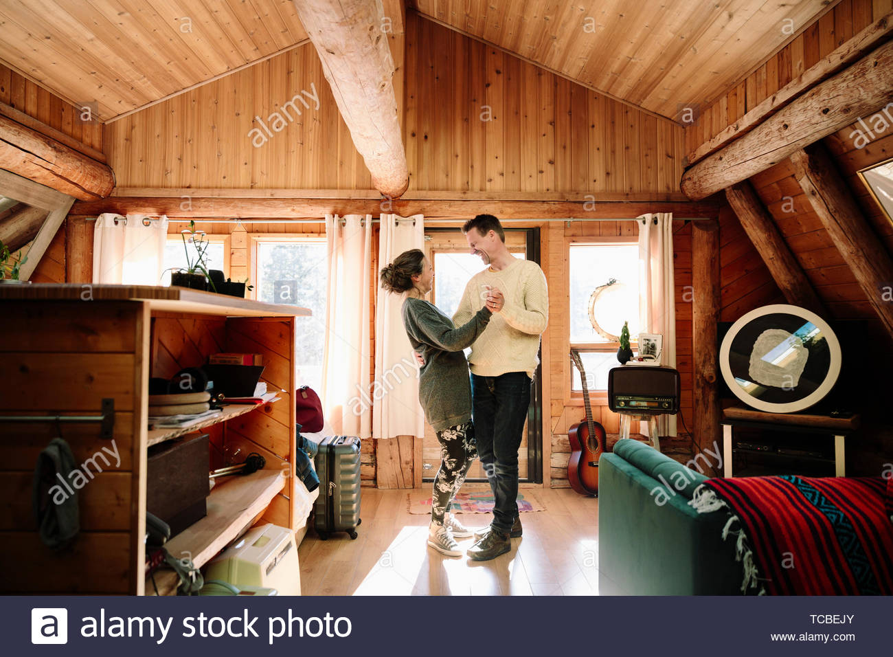 Affectionate couple dancing in cabin Stock Photo
