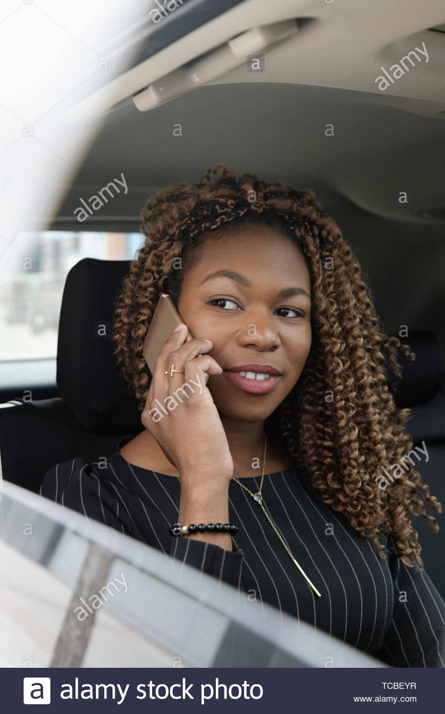 Businesswoman talking on smart phone in back seat of crowdsourced taxi - Stock Image