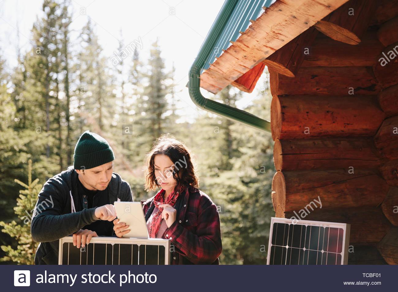 Couple using digital tablet, installing solar panels outside cabin - Stock Image