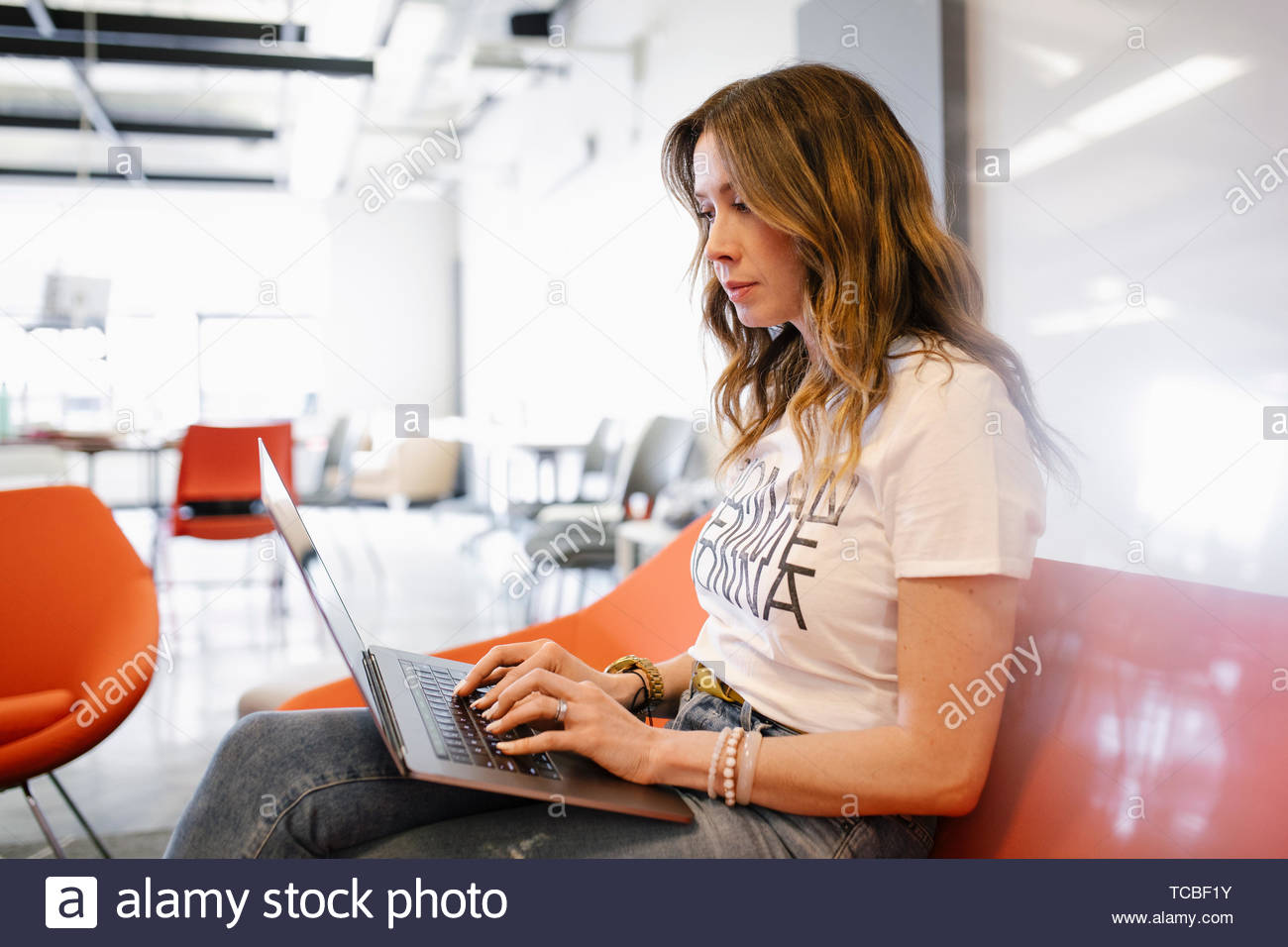 Businesswoman using laptop in coworking space - Stock Image