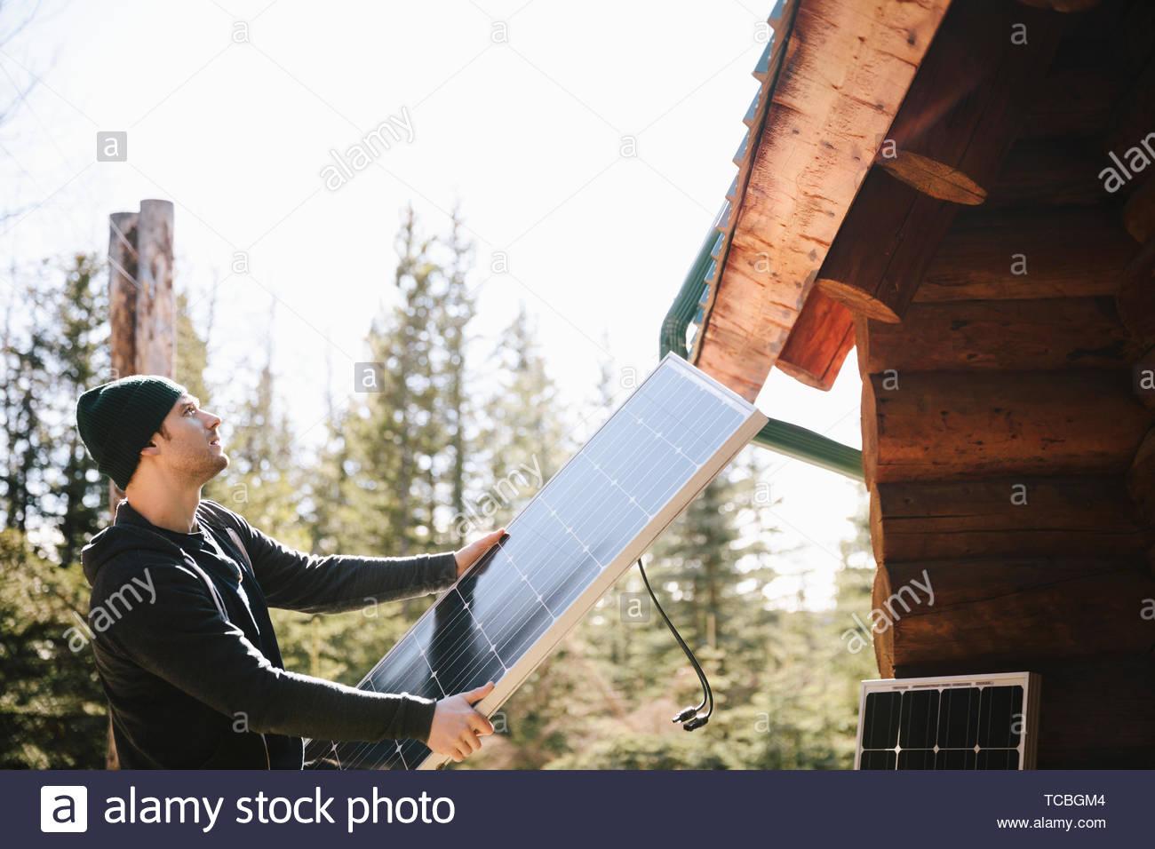Man installing solar panels outside cabin - Stock Image