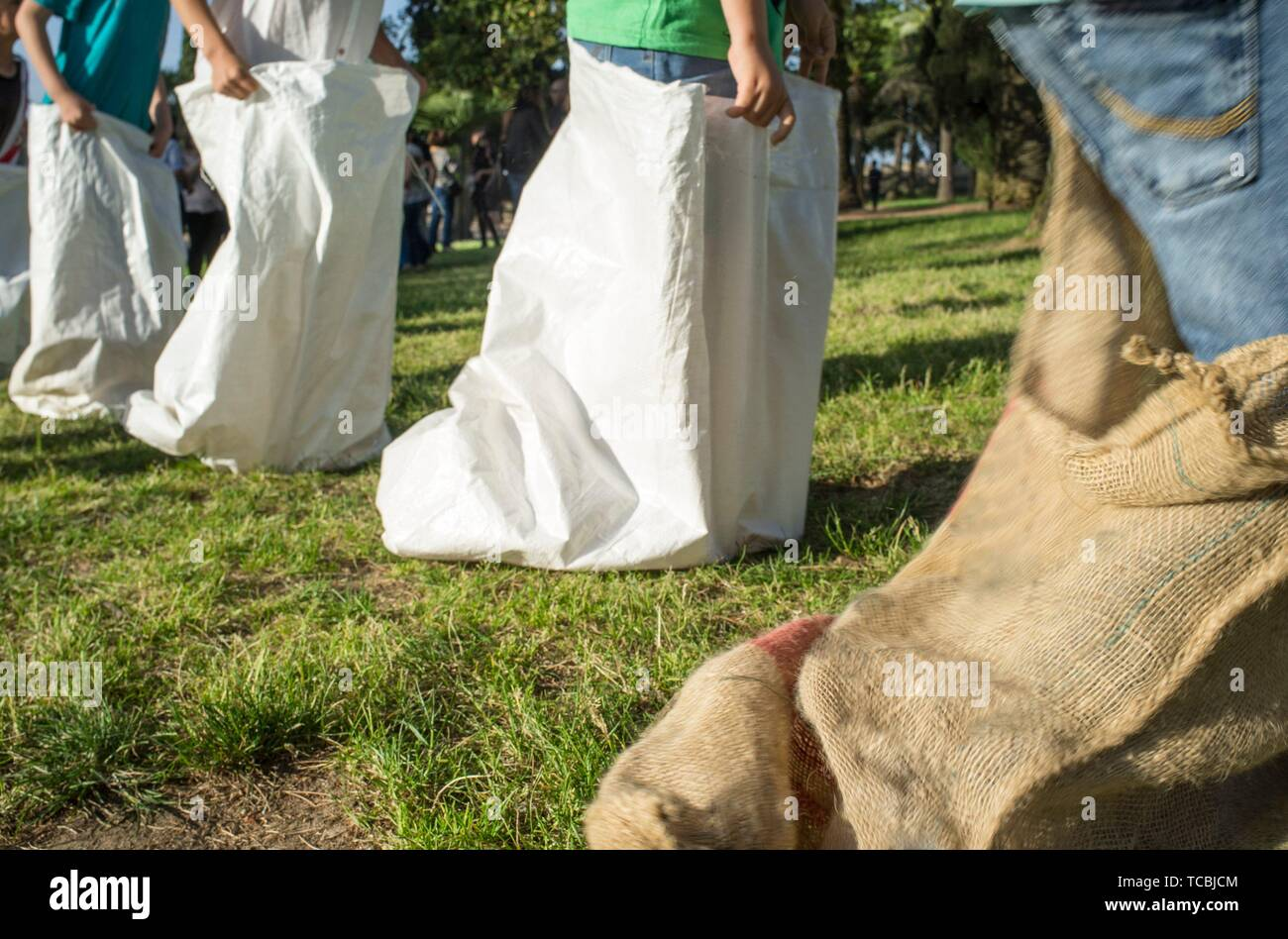 Children having a sack race in the park. Classic games concept. Motion blurred. - Stock Image