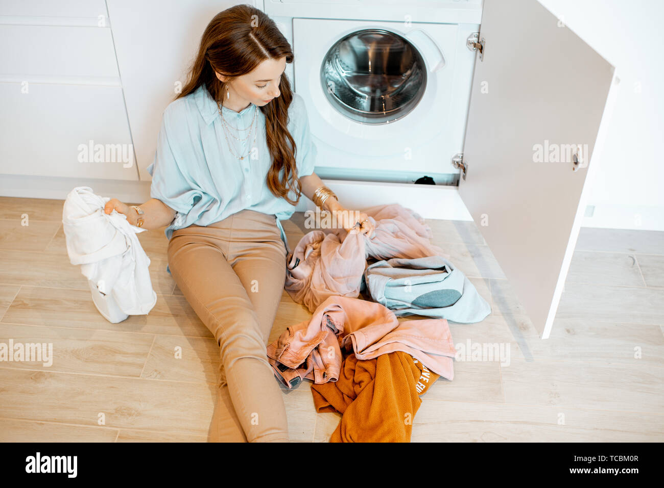 Young Woman Sorting Dirty Clothes While Sitting On The Floor Near
