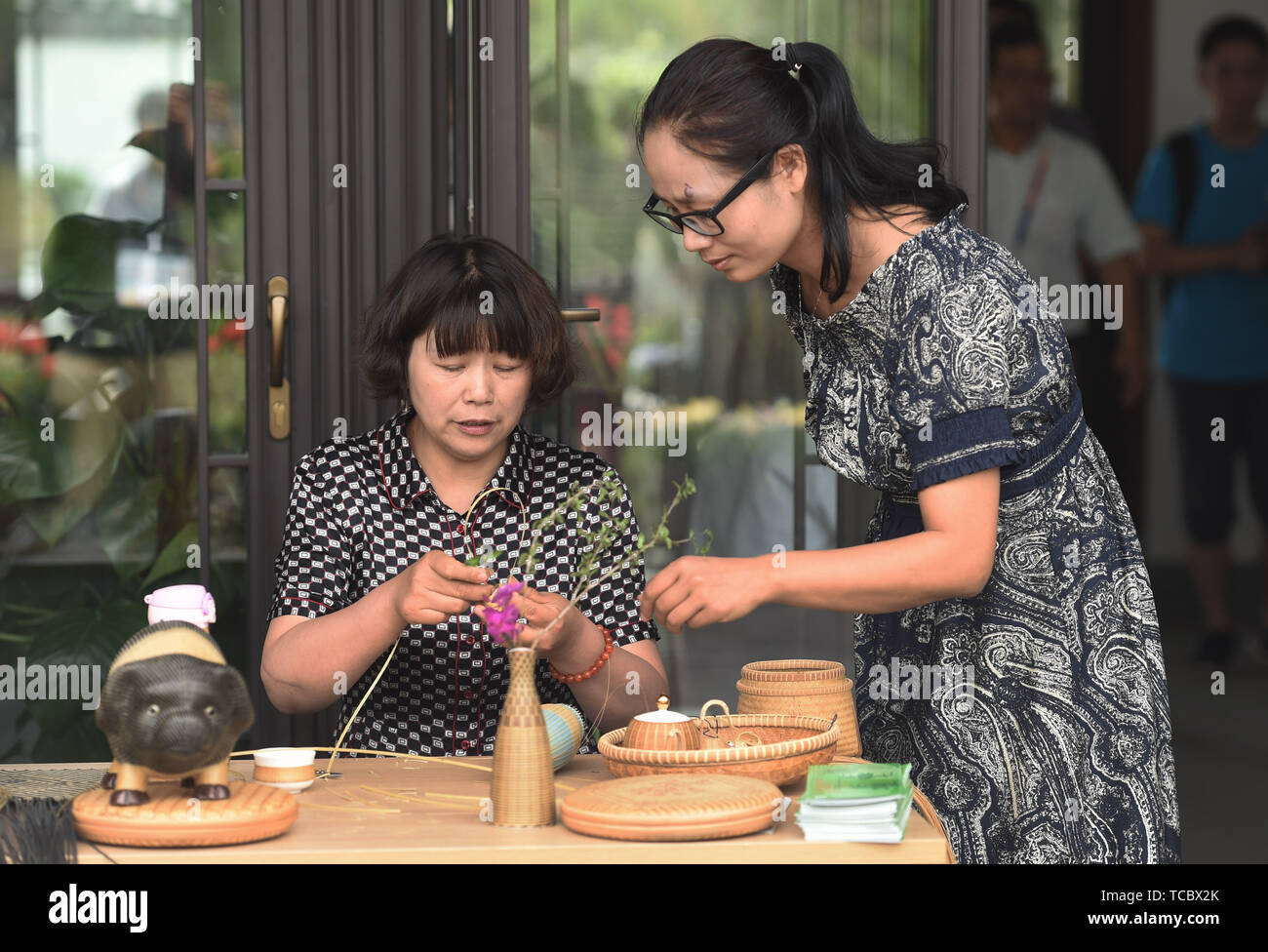Beijing, China. 6th June, 2019. Visitors learn about bamboo weaving during the 'Zhejiang Day' theme event at the Beijing International Horticultural Exhibition in Yanqing District, Beijing, capital of China, June 6, 2019. The Beijing International Horticultural Exhibition will display Zhejiang's achievements in ecological development with a Zhejiang Day theme event from June 6 to 8. Credit: Ren Chao/Xinhua/Alamy Live News - Stock Image