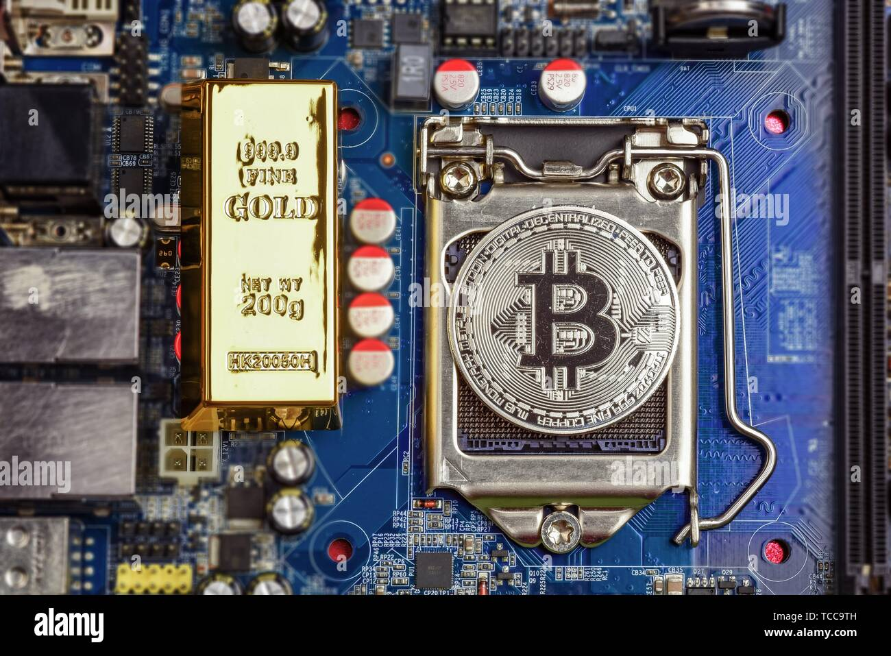 Top view of golden bit coin and golden brick or block on computer mother board processor. Bitcoin mining farm, working computer equipment concept. - Stock Image