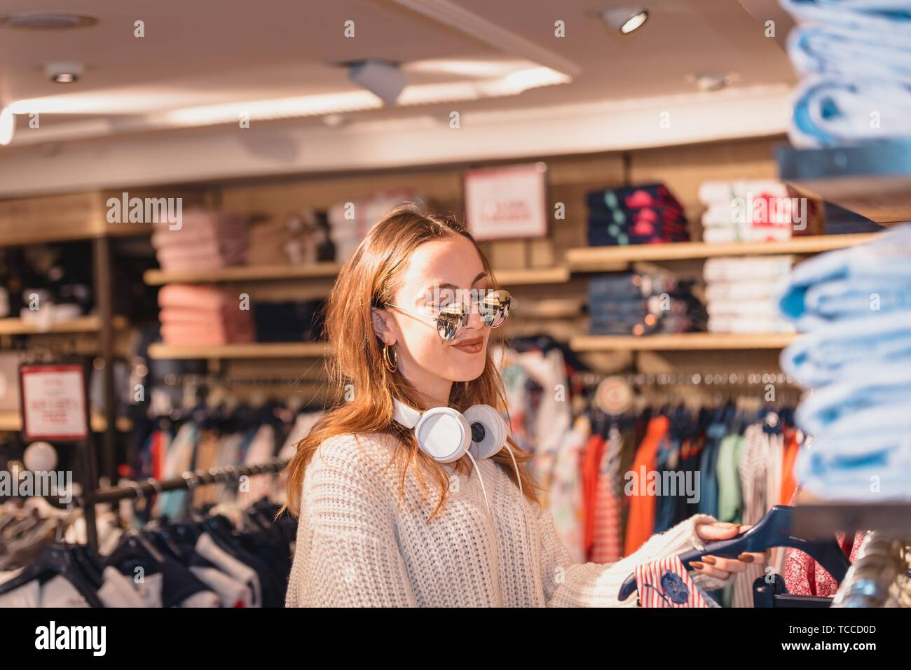 Beautiful attractive young girl in jumper with headphone and sunglasses chooses clothes thinking looking at clothing while shopping in store. Stock Photo