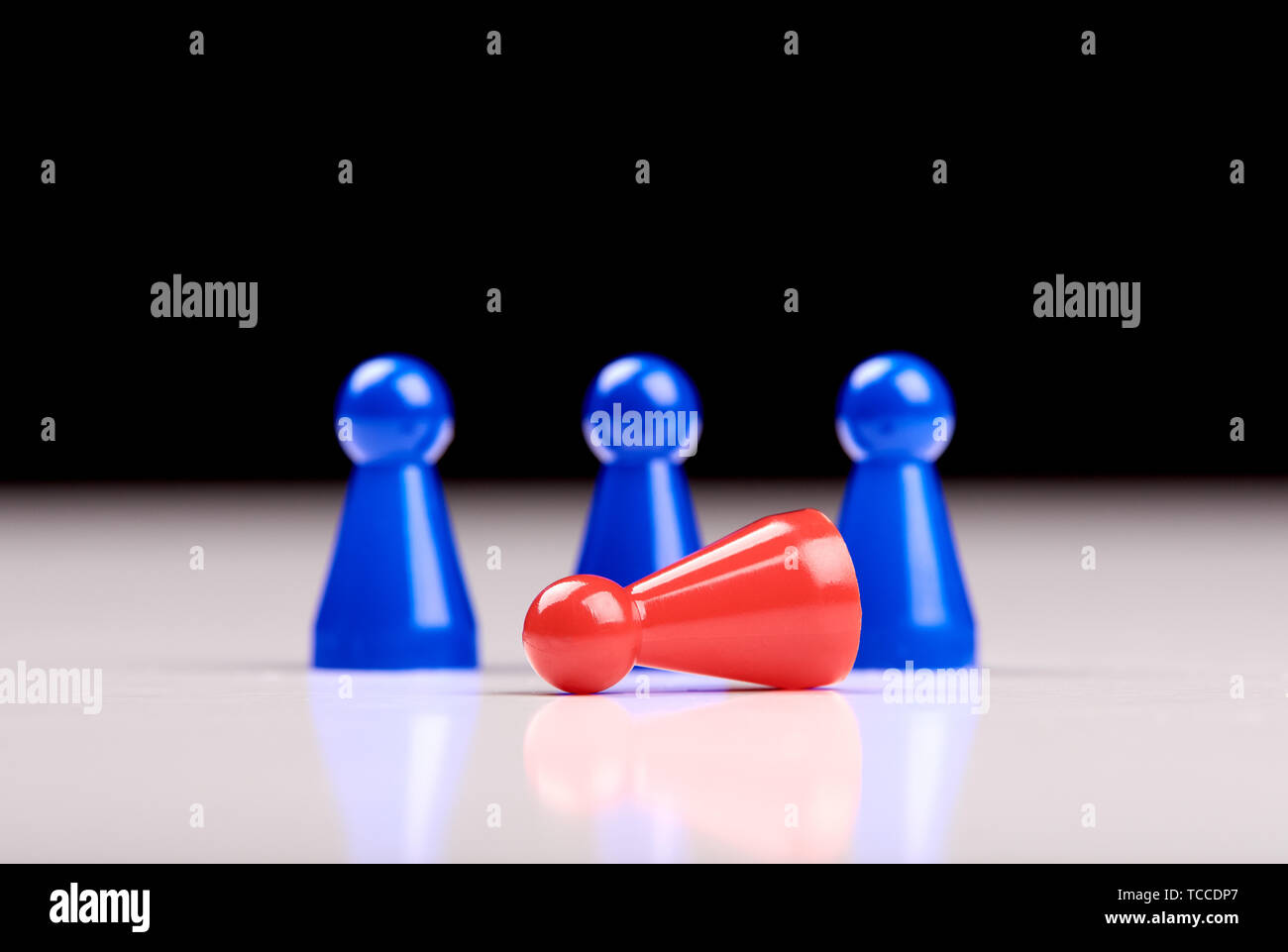 Standing three blue game pieces as winner and lying red figurine as loser on white table top with black background. Space for your text. - Stock Image