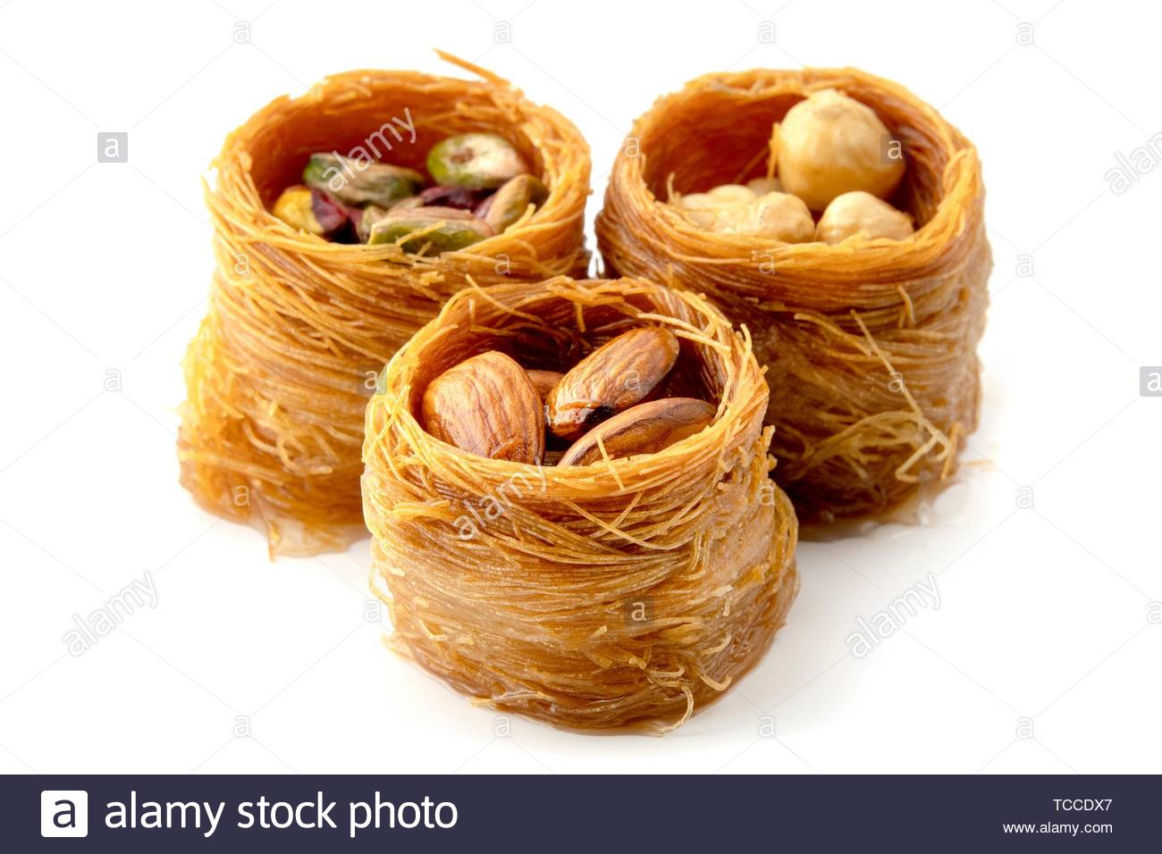 Mixed Bird nest baklava with almonds, nuts and pistachios on a white background. - Stock Image