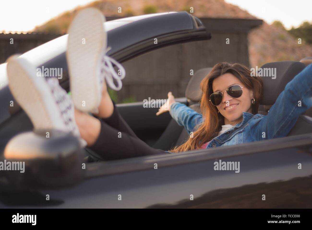 Happy young woman enjoying her convertible car. - Stock Image