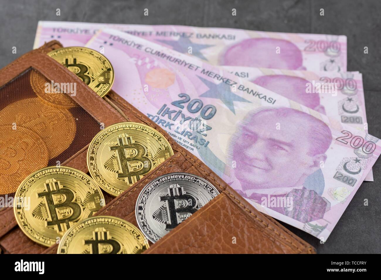 View of metal bitcoins in brown leather wallet and over Turkish Lira banknotes. Concept image for cryptocurrency. Stock Photo