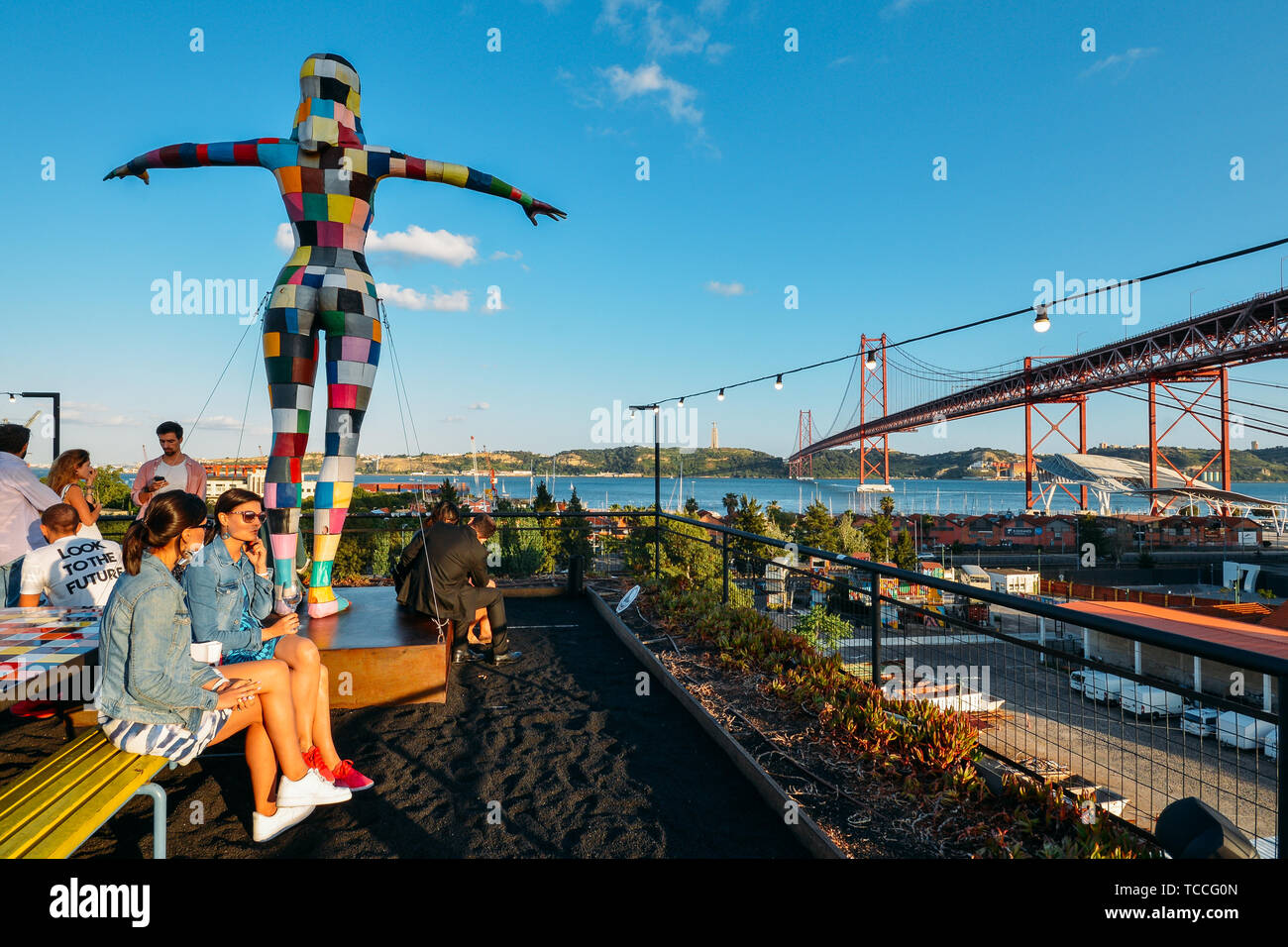 Lisbon, Portugal - June 5, 2019: View of 25th of April bridge with people sitting on the bar terrace at LX Factory in Alcantara - Stock Image