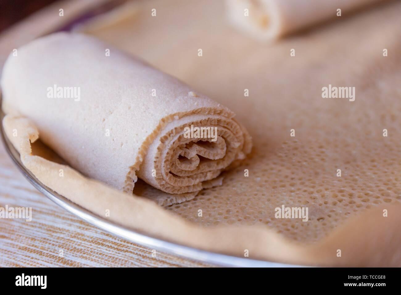 Injera is a sourdough flatbread made from teff flour. It is the national dish of Ethiopia, Eritrea, Somalia and Djibouti. Stock Photo