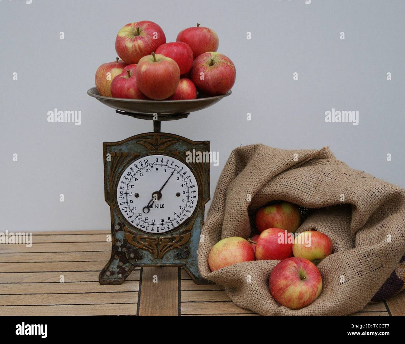 On wooden background the nostalgic kitchen scale with dial next to a bag filled with apples - Stock Image