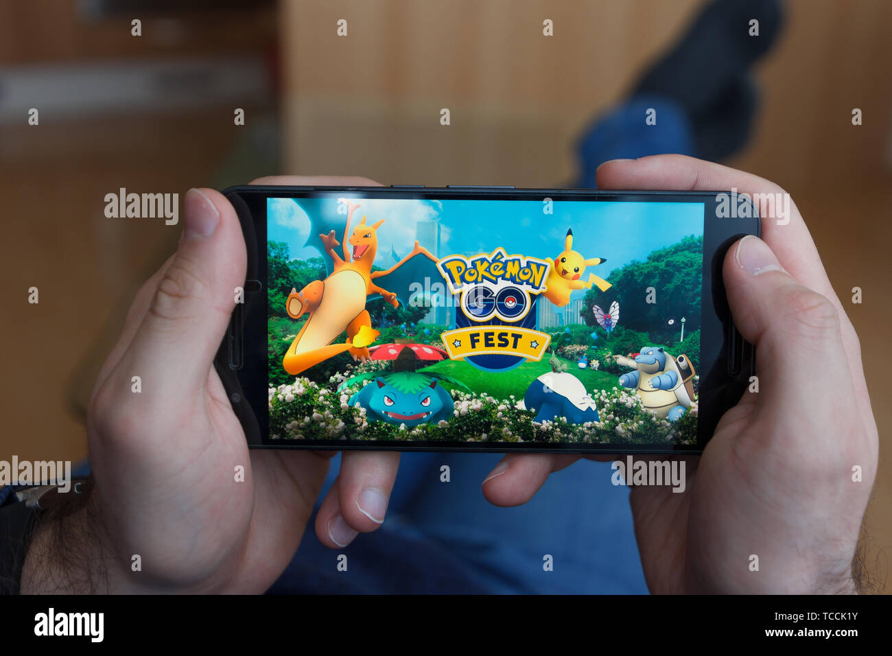 LOS ANGELES, CALIFORNIA - JUNE 3, 2019: Lying Man holding a smartphone and playing the Pokemon Go game on the smartphone screen. An illustrative edito Stock Photo