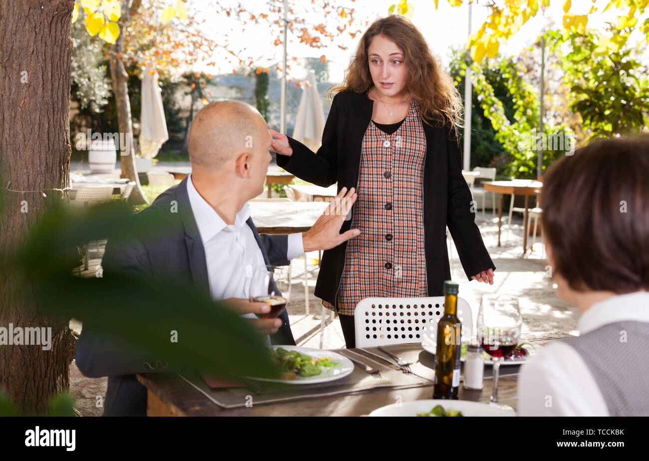 Family quarrel during lunch in an open-air restaurant - Stock Image