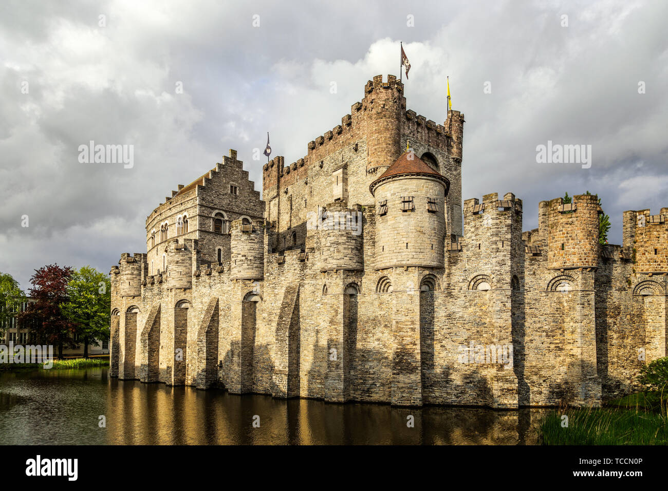 Fortified walls and towers of Gravensteen medieval castle with moat in the foreground, Ghent East Flanders, Belgium Stock Photo
